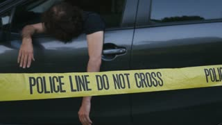 Injured or dead caucasian man hanging out of car crime scene behind police line do not cross