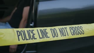 Injured or dead caucasian man in the driver seat of car crime scene behind police line do not cross