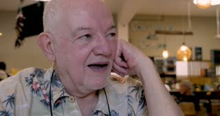 Jovial happy elderly senior man in his 70s or early 80s laughing out loud in a restaurant or cafe