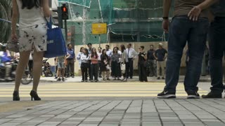 KUALA LUMPUR, MALAYSIA - CIRCA FEBRUARY 2018 - Asian people waiting at a crosswalk for a traffic light to cross a busy street - low angle slow motion