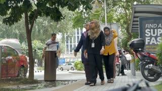 KUALA LUMPUR, MALAYSIA - CIRCA FEBRUARY 2018 - Malaysian business women in burqas wearing lanyards walking on a side walk in slow motion
