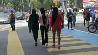 KUALA LUMPUR, MALAYSIA - CIRCA FEBRUARY 2018 - Malaysian people including muslim women wearing burkas walking through a crosswalk in the city during the day in slow motion