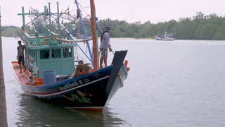 LANGSUAN, CHUMPHON, THAILAND - CIRCA FEB 2017 - Thai squid fishing boat with fishermen turning around and going out toward sea