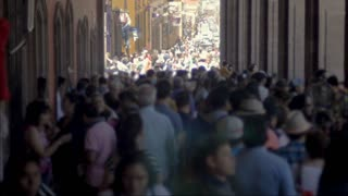 Large anonymous crowd of people walking in the streets and sidewalks during the day - blurred background plate
