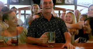 Large group of people patting and cheering a man sitting at a bar like they are celebrating his birthday or special event