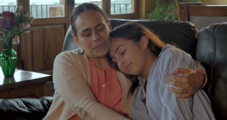 Latino Mom comforting and quietly hugging her upset teenage daughter - dolly shot