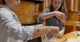 Latino mother and daughter sprinkling flour on dough while cooking and baking together in their kitchen