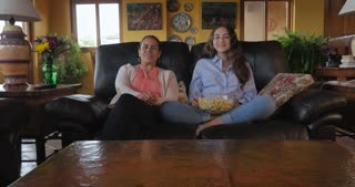 Latino mother and teenager daughter watching tv on the sofa eating popcorn and changing the channels with the remote - push in gimbal shot