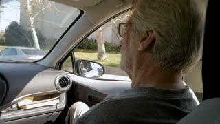 Los Angeles, UNITED STATES - CIRCA FEBRUARY 2018 - Elderly senior man sitting in the passenger seat of a car being driven through a suburban part of the city in slow motion