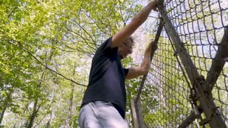 Low angle of a man carefully climbing over a chainlink fence breaking into private property in slow motion