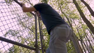 Low angle of a man climbing over a chain link fence trespassing in private property in slow motion