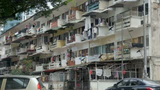 Low income apartments with laundry hanging from porches of each living space