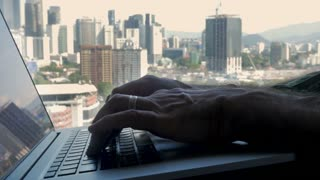 Male hands typing on a laptop computer overlooking a modern busy city - slow motion push out