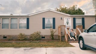 Man and woman couple sitting on porch steps of their manufactured home high five each other - wide dolly shot