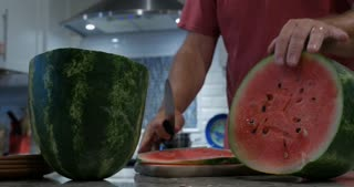 Man and woman working together to put sliced watermelon on plates in a modern kitchen