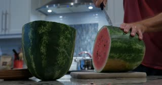 Man cutting a large watermelon with a knife in his kitchen