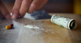 Man filling an empty capsule a white powder signifying fake or counterfeit drugs