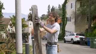 Man homeowner wearing work gloves repairing a fence outside a neighborhood in Southern California stabilized shot