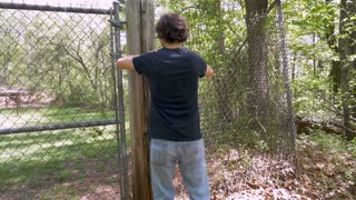 Man in his 30s or 40s breaking through a chain link fence and running into the woods in slow motion