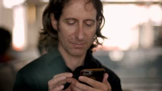Man in his 30s or 40s using smart phone looks up at camera and smiles in slow motion inside a public place