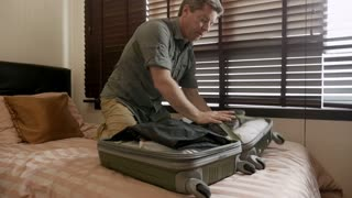Man in late 40s or early 50s having a hard time packing his overstuffed suitcase in slow motion