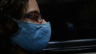 Man sitting next to a window of a subway wearing a respiratory face mask and glasses