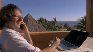 Man talking on smart phone while working in home office on his laptop computer overlooking the beach in slow motion