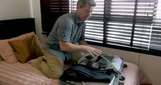 Man trying to close his overstuffed travel bag drops his luggage on the floor while packing for a trip