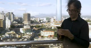 Man typing on a mobile phone overlooking a large city standing outside on a rooftop smiles and looks up at the camera