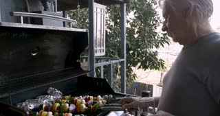 Man walks up to an older senior man both holding drinks and helps him grilling vegetable shish kebabs on a BBQ grill