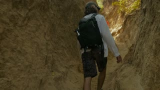 Man wearing a daypack backpack walking and hiking through a narrow path touching the rocky wall with his finger in slow motion