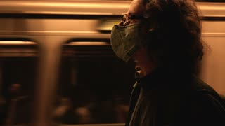 Man wearing a face mask as a moving subway train goes by in slow motion