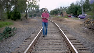 Man wearing a hat walking on railroad tracks while looking down at and using his smart phone in slow motion