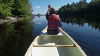 Man wearing a personal floatation device paddling from the front of a canoe in a calm pristine mountain lake or river in slow motion on a beautiful day