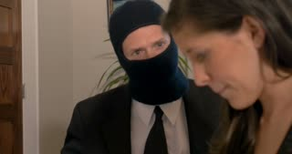 Man wearing a ski face mask and suit and tie getting a woman to sign paperwork concept scam, shady deal, or corrupt business
