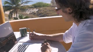 Man writing with pen and paper while working on laptop computer with charts and graphs outside his home office