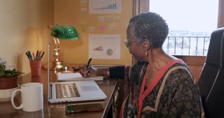 Mature attractive black woman writing in a notebook in her home or remote office - push in