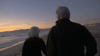 Mature fit active retired 60s couple walking on beach during sunset or sunrise from behind in slow motion