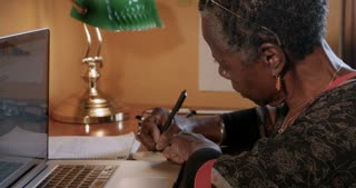 Mature professional black woman writing reminders on yellow sticky notes and posting them on her wall in her office