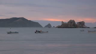 Men prepare their boats for their morning fishing on the ocean as a pelican flies by.