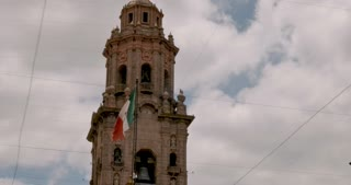 Mexican flag flying next to a bell tower of the Morelia Cathedral filmed from inside the courtyard of the Michoacan State Government Palace