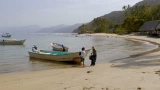 Mexican man and woman getting off a water taxi in a calm bay off a boat and walking on an empty beach with a few thatched roof buildings in slow motion