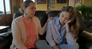 Mexican mom helping her depressed sad teenage daughter by consoling her - push in