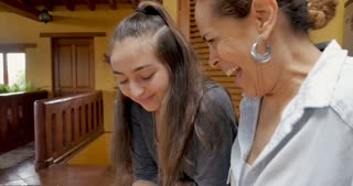 Mexican mother and mixed race teenager daughter laughing together while using a cell phone - push out gimbal shot