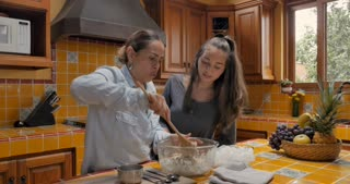 Mexican mother mixing dough while her teenager daughter watches and learns - push in gimbal shot