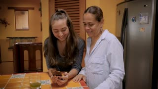 Mexican or latino mother and teenager daughter looking at a cell phone together and laughing in their kitchen - slow motion gimbal shot