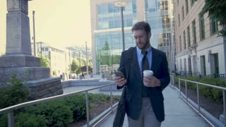 Millennial corporate executive businessman leaving his modern office building walking and using mobile device technology app in slow motion stabilized shot