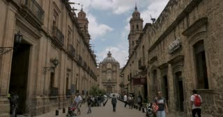 MORELIA, MEXICO - CIRCA AUGUST 2018 - Camera approaching the Morelia Cathedral up Benito Juarez street with pedestrians only - gimbal stabilized shot