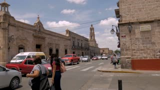 MORELIA, MEXICO - CIRCA AUGUST 2018 - Two Mexican women waiting at a crosswalk to cross the busy street of Avenida Francisco I. Madero filled with traffic