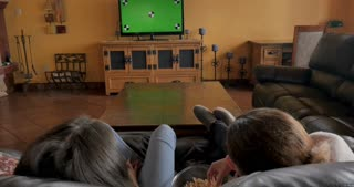 Mother and teen daughter watching a green screen tv and eating popcorn in their living room - shot from behind wide angle